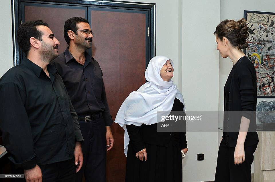 A picture uploaded on the official page of the Syrian Presidency on the internet social network site, Facebook, on October 1, 2013, shows Syrian first lady, Asma al-Assad (R), speaks to an old woman during a reported meeting with family members of martyrs, in the capital Damascus. AFP PHOTO / FACEBOOK == RESTRICTED TO EDITORIAL USE - MANDATORY CREDIT 'AFP PHOTO / FACEBOOK' - NO
