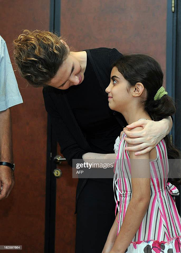 A picture uploaded on the official page of the Syrian Presidency on the internet social network site, Facebook, on October 1, 2013, shows Syrian first lady, Asma al-Assad (L), speaking with a young girl during a reported meeting with family members of martyrs, in the capital Damascus. AFP PHOTO / FACEBOOK == RESTRICTED TO EDITORIAL USE - MANDATORY CREDIT 'AFP PHOTO / FACEBOOK' - NO