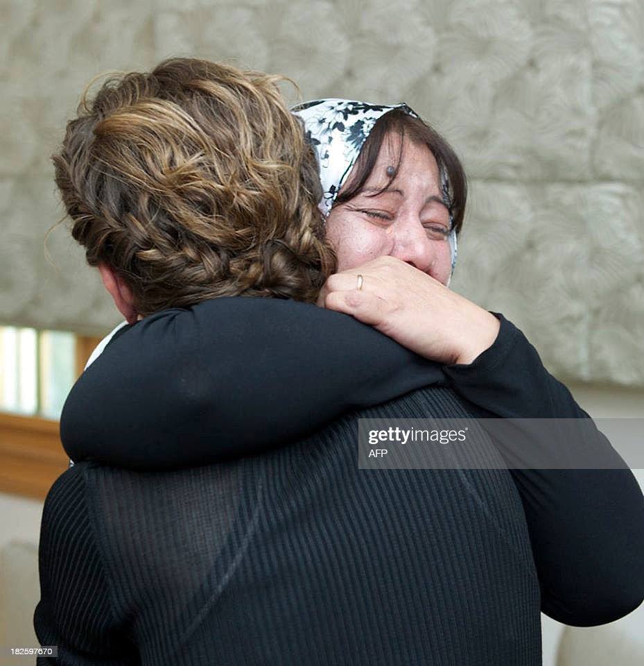 A picture uploaded on the official page of the Syrian Presidency on the internet social network site, Facebook, on October 1, 2013, shows Syrian first lady, Asma al-Assad (R), hugging a crying women during a reported meeting with family members of martyrs, in the capital Damascus. AFP PHOTO / FACEBOOK == RESTRICTED TO EDITORIAL USE - MANDATORY CREDIT 'AFP PHOTO / FACEBOOK' - NO MARKETING NO ADVERTISING CAMPAIGNS - DISTRIBUTED AS A SERVICE TO CLIENTS ==