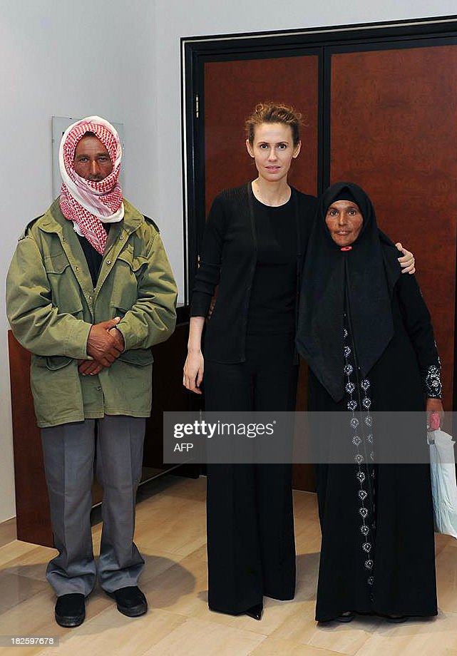 A picture uploaded on the official page of the Syrian Presidency on the internet social network site, Facebook, on October 1, 2013, shows Syrian first lady, Asma al-Assad (C), posing for a picture with family members of martyrs according to reports, in the capital Damascus. AFP PHOTO / FACEBOOK == RESTRICTED TO EDITORIAL USE - MANDATORY CREDIT 'AFP PHOTO / FACEBOOK' - NO