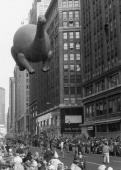 A bronchiosaurus balloon floats high above the crowd during the 1974 Macy's Thanksgiving Day Parade
