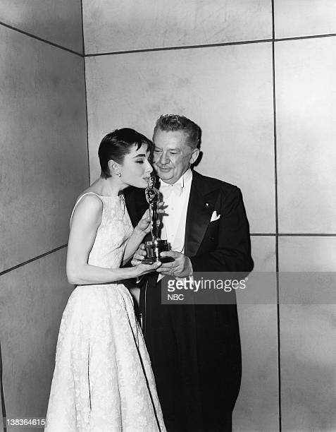 Actress Audrey Hepburn wearing a Givenchy gown kisses her 'Best Actress in a Leading Role' award for 'Roman Holiday' and Danish actor Jean Hersholt...