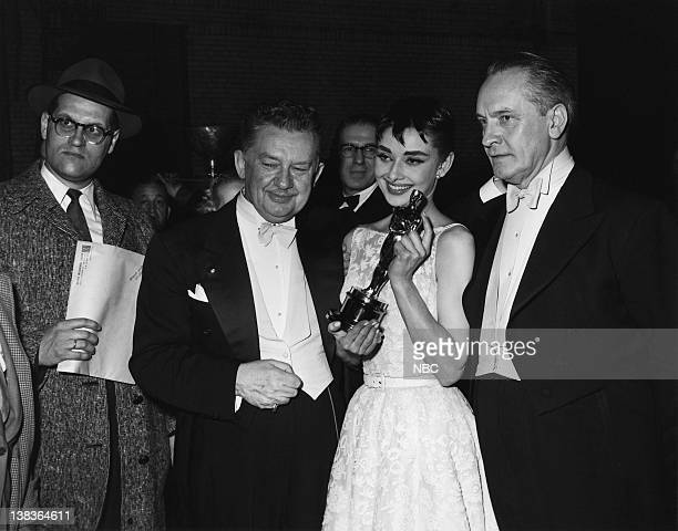 Danish actor Jean Hersholt actress Audrey Hepburn wearing a Givenchy gown and actor Frederick March during the 26th Annual Academy Awards at the NBC...