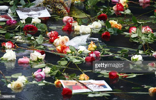 Pictures and flowers float in the reflecting pool during a ceremony commemorating the 911 terrorist attacks at the World Trade Center site September...