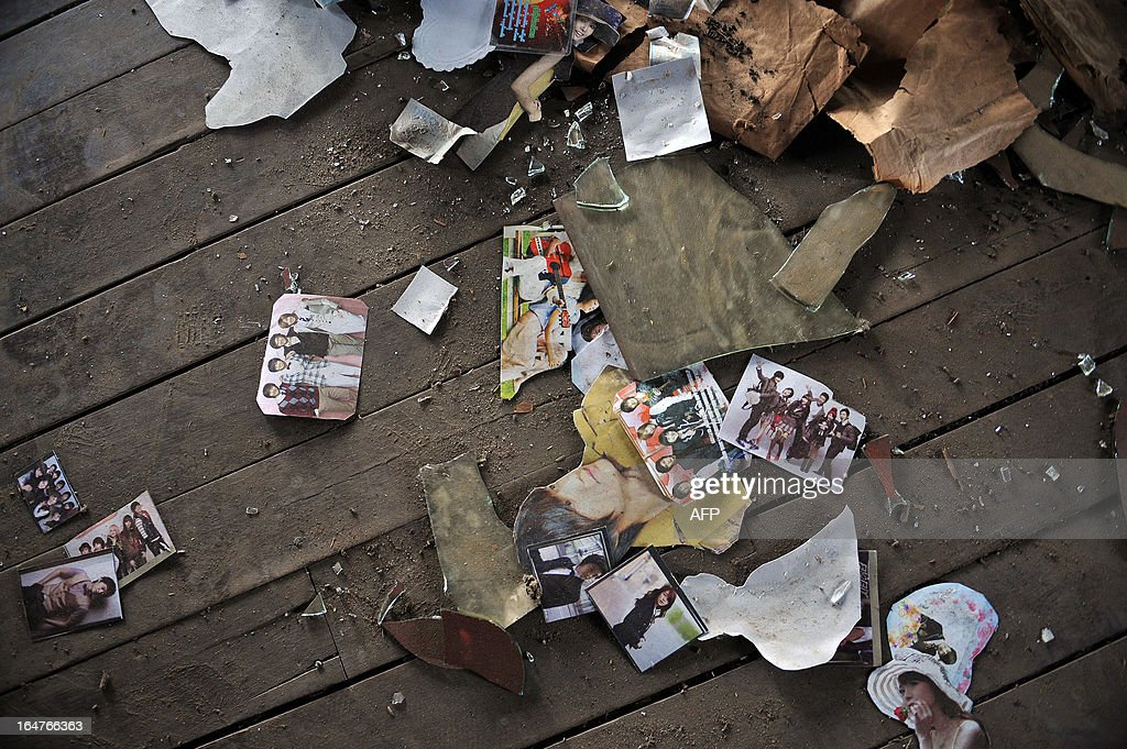 Pictures lie on the floor of a ransacked house after sectarian violence spread through central Myanmar, in Zeegone, Bago division on March 28, 2013. A mosque and Muslim homes were destroyed by hundreds of people in the town of Zeegone about 150 kilometres (90 miles) north of the country's main city Yangon on March 27, the latest outbreak of violence in communal unrest that has left at least 40 people dead. AFP PHOTO/Ye Aung THU