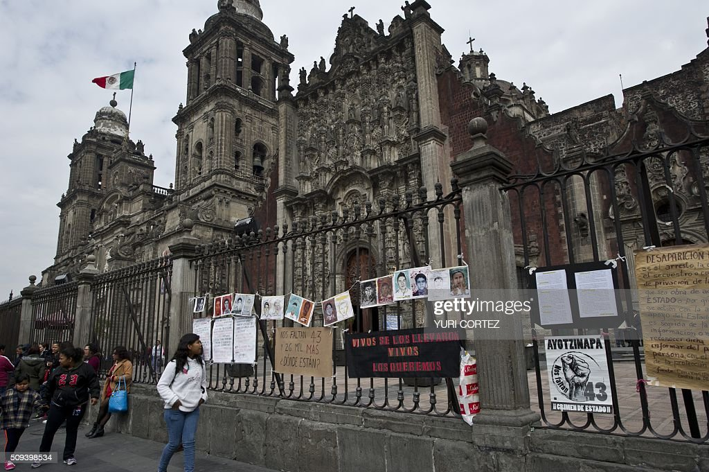 Pictures of disappeared people hang from the fence of the main Cathedral which Pope Francis is due to visit, in Mexico City on February 10, 2016. Pope Francis will visit four Mexican states from next February 12 to 17. AFP PHOTO / YURI CORTEZ / AFP / YURI CORTEZ