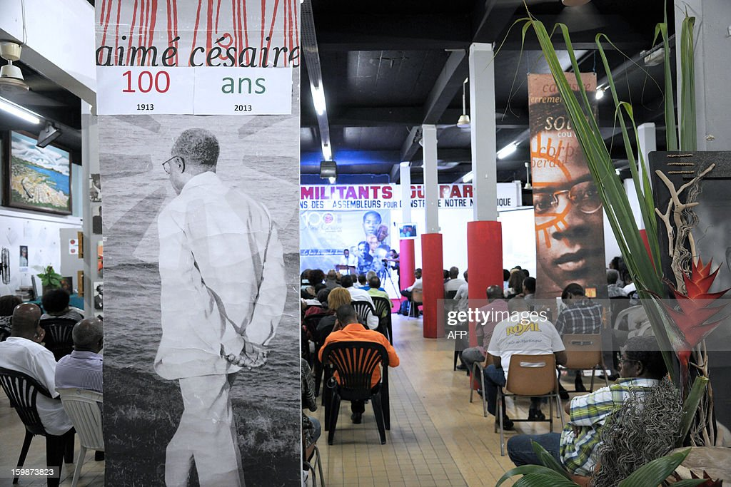 Pictures of late French poet and politician Aime Cesaire (C) are displayed on January 21, 2013 at the Martinican Progressive Party (PPM) headquarters in Fort-de-France, on the French Caribbean island of Martinique, marking the 100th anniversary of Cesaire's birth. Cesaire (June 25, 1913 – 17 April 2008) was former mayor of Fort-de-France and had funded the PPM party in 1958. As a pioneer of the black pride movement, Cesaire was a cult figure on his native island of Martinique and in the French-speaking world. With fellow writers such as Leopold Sedar Senghor of Senegal, 'Papa Cesaire' invented the term 'negritude,' which he defined as an 'affirmation that one is black and proud of it', decades before the emergence of Steve Biko or Martin Luther King. AFP PHOTO JEAN-MICHEL ANDRE