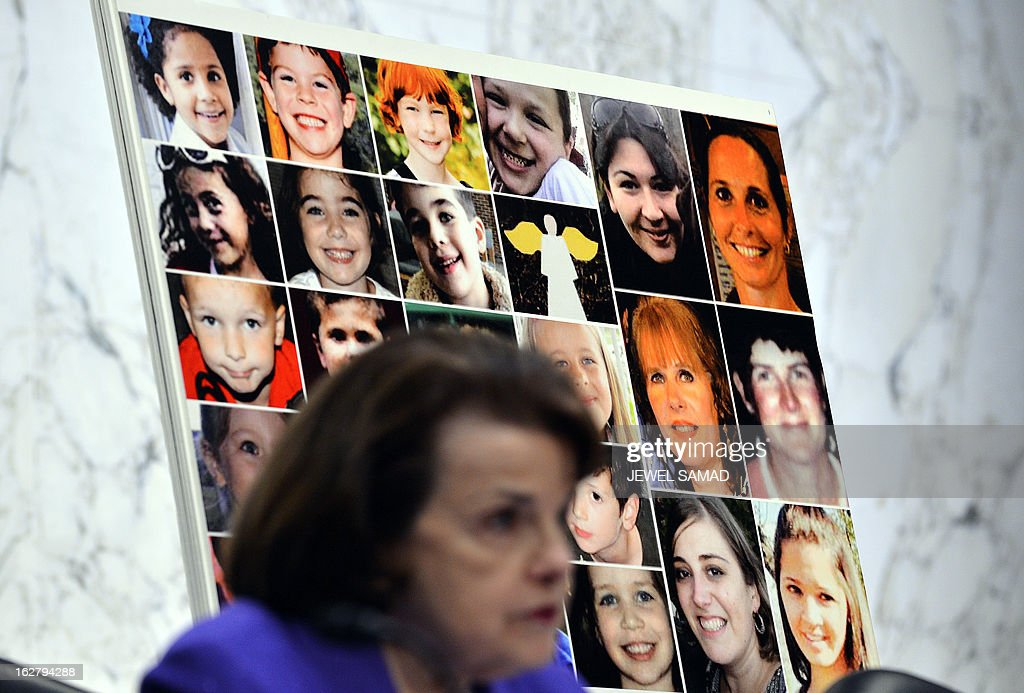 Pictures of Newtown's Sandy Hook Elementary School shooting victims are displayed as Senate Judiciary Committee chairperson Dianne Feinstein speaks during a hearing on 'The Assault Weapons Ban of 2013' at the Hart Senate Office Building in Washington, DC, on February 27, 2013. AFP PHOTO/Jewel Samad