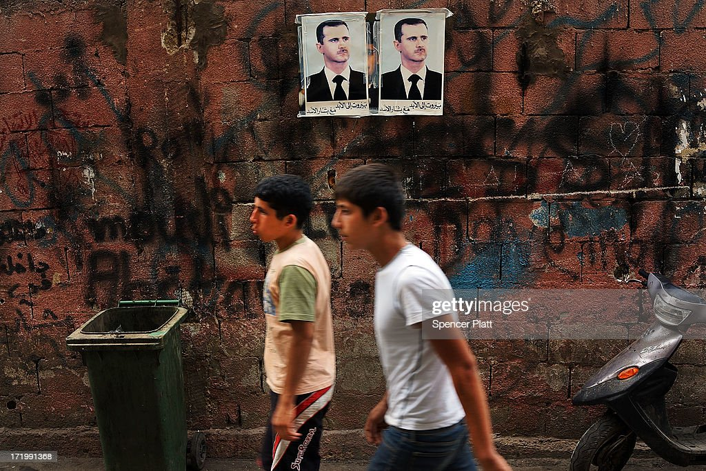 Pictures of Syrian president Bashar al-Assad are viewed along a wall in a poor, Hezbollah influenced neighborhood with a high concentration of Syrian refugees on June 30, 2013 in Beirut, Lebanon. Currently the Lebanese government officially hosts 546,000 Syrians with an estimated additional 500,000 who have not registered with the United Nations. Lebanon, a country of only 4 million people, is now home to the largest number of Syrian refugees who have fled the conflict. The situation is beginning to put a huge social and political strains on Lebanon as there is currently no end in sight to the war in Syria.