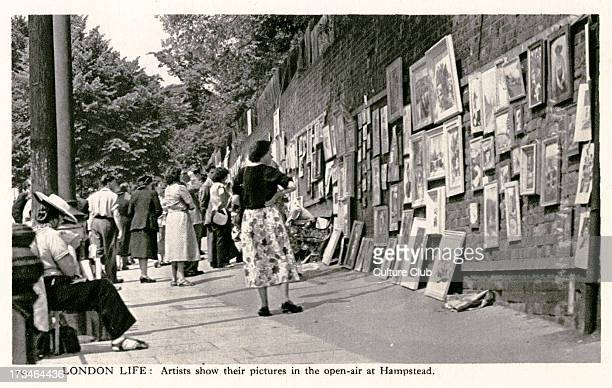 Pictures shown in the openair at Hampstead Heath London Passersby browse the pictures hanging on the walls