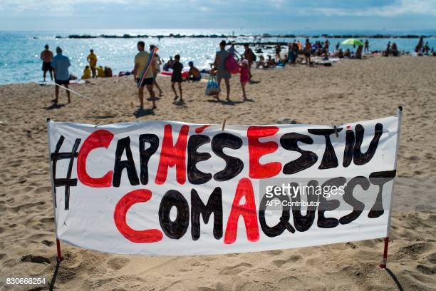 Pictures shows a banner on La Barceloneta beach reading in Catalan 'Never again a summer like this' during a protest against 'drunken tourism' called...