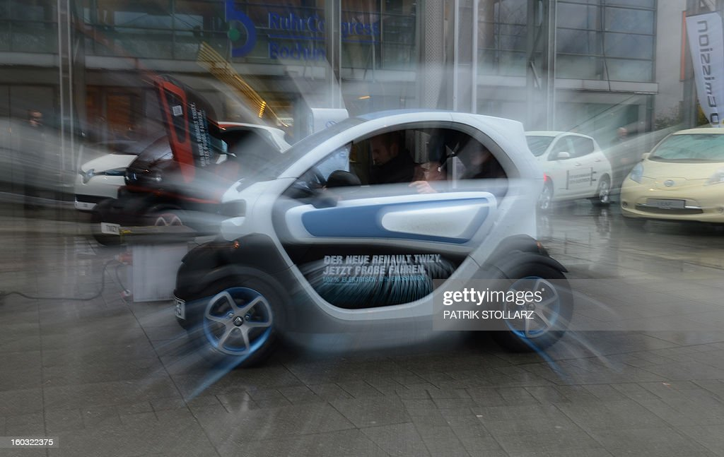 Picturte taken with a zoom effect shows a man driving a Renault Twizy for a test ride during the CAR-Symposium in Bochum, western Germany, on January 29, 2013. Automotive distributers and major car companies discuss about the future of the automotive industries. AFP PHOTO / PATRIK STOLLARZ
