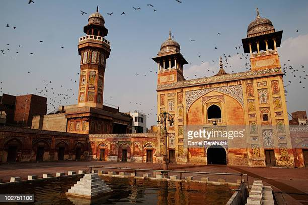 Pidgeons fly over the Wazir Khan Mosque in the walled city of Old Lahore on July 9 2010 in Lahore Pakistan The Mosque was built in 163435 during the...