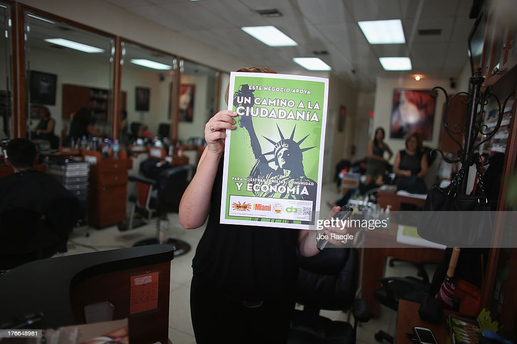 Pie Dad Botero holds up a poster in the beauty salon she works which translated from Spanish to English reads, ' A path to citizenship,' after she received it from immigration activists looking for support for immigration reform from businesses on August 16, 2013 in Miami, Florida. The protesters were targeting their message toward Representatives Ileana Ros-Lehtinen and Mario Diaz-Balart to do more to win Comprehensive Immigration Reform with a path to citizenship.