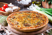 Pie with mushrooms, chicken on wooden kitchen board. Traditional French food.