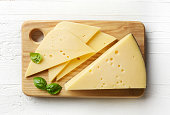 Cutting board of cheese on white wooden background. From top view