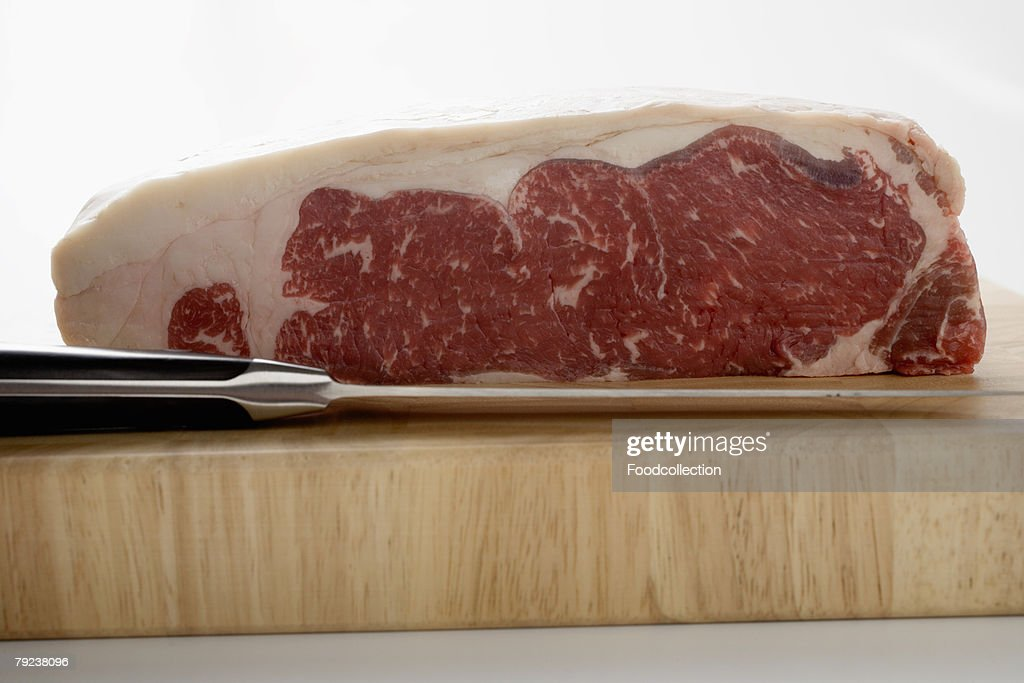 A piece of beef sirloin on wooden board with knife : Stock Photo