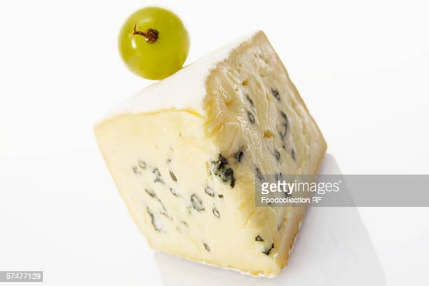 A piece of blue cheese with a single grape