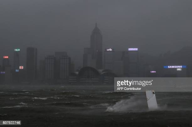 TOPSHOT A piece of debris carried by winds from Typhoon Hato is blown across Victoria harbour as dark skies hover over the Hong Kong island skyline...