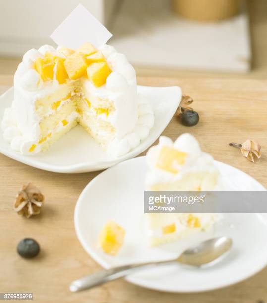 A piece of fruit cream cake on a white plate is placed on the table