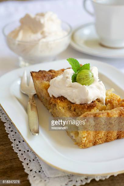 Piece of gooseberry almond tart with cream on plate