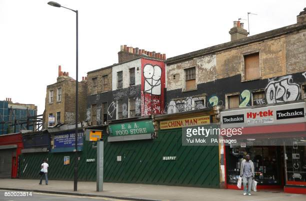 A piece of graffiti on the side of derelict flats above shops in Dalston east London by street artist Stik