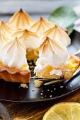 Plate of lemon tart and meringue on wooden table, selective focus.