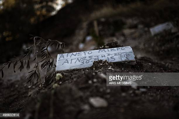 A piece of marble reading 'Unidentified child' is placed over the grave of a child who drowned on its way from Turkey to the Greek island of Lesbos...