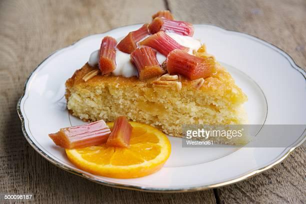 Piece of orange almond semolina cake with baked rhubarb, served with soy yogurt