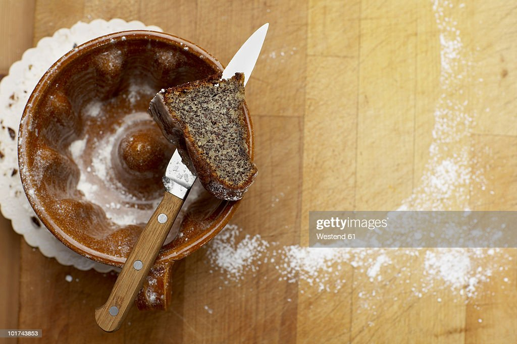 Piece of poppy seed cake on knife, elevated view