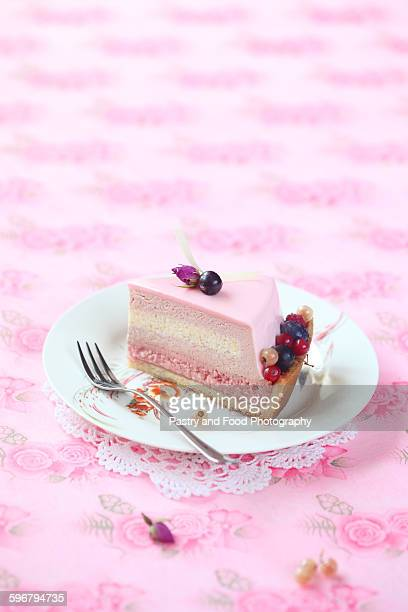 Piece of red currant, rose and lychee mousse cake