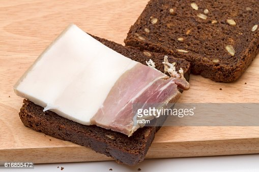 Piece of salty bacon on rye bread : Stock Photo