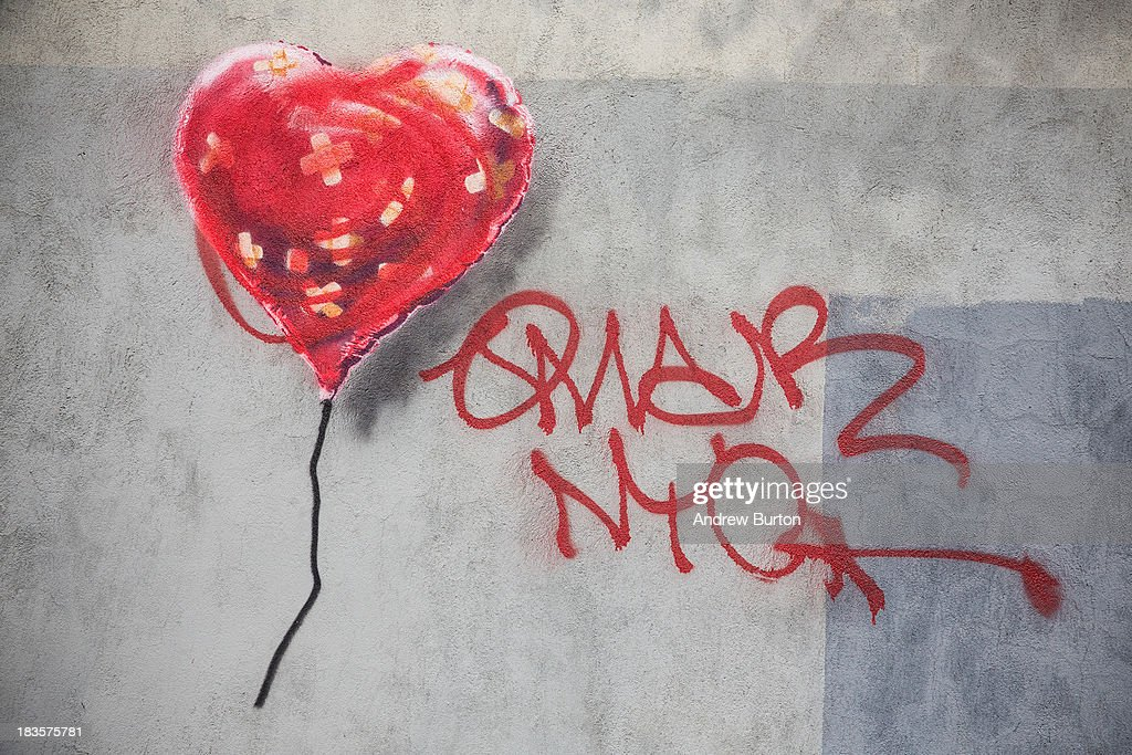 A piece of street art depicting a heart-shaped balloon covered in bandages, allegedly done by the street artist Banksy, is seen on October 7, 2013 in the Red Hook neighborhood of the Brooklyn borough of New York City. The piece was defaced with red spray paint shortly after being completed.