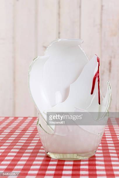 Pieces of broken white flower vase with blood