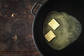 Pieces of butter in the hot pan  on the metal background top view