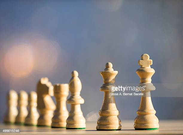 Pieces of chess in rows on a board of wood outdoors illuminated by the light of the Sun