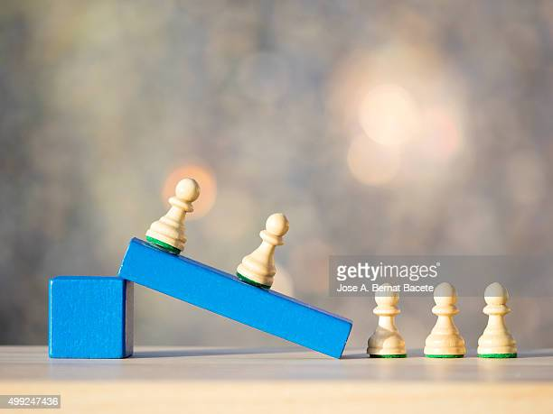 Pieces of chess on blocks of wood of toy representing persons