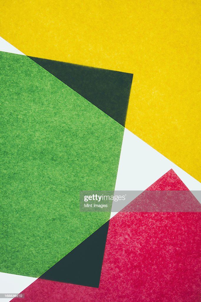 Pieces of colorful, recycled construction paper, overlapping and laid out at random.