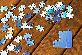 Pieces of different puzzles on a wooden table. The concept of thinking development.