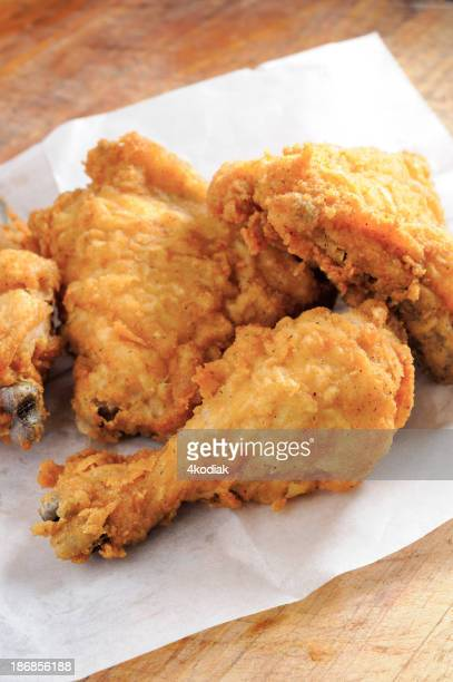 Pieces of fried chicken on a tissue in a wooden table