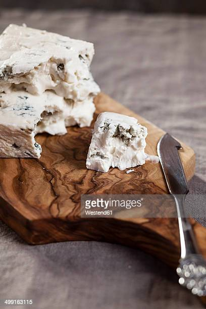 Pieces of gorgonzola cheese on chopping board