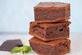 Pieces of healthy vegan chocolate brownie on slate board. Healthy vegetarian dessert concept.