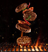 Pieces of minced meal for hamburgers flying above grill grid. Barbecue and grill