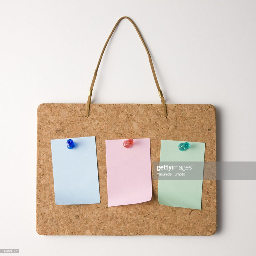 Pieces of paper are sticked with pins on a cork board. : Stock Photo