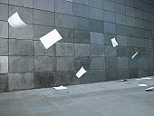 Pieces of paper blowing along street