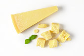 wedge and pieces of fresh parmesan cheese on white background