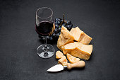 pieces of parmesan or parmigiano hard cheese, wine and grapes on dark concrete background