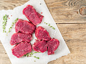 Pieces of raw meat. Raw beef with spices and thyme on white parchment paper on wooden rough rustic background, top view, close up, copy space.
