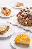 Pieces of tart around tart with cream puffs and strawberry, white background