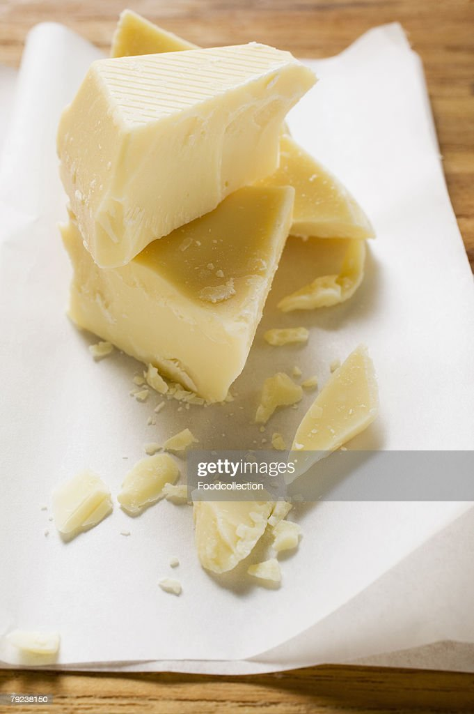 Pieces of white chocolate on paper : Stock Photo
